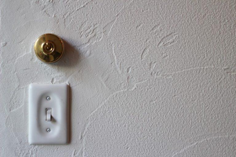 白い漆喰壁に金色のアインティークスイッチが付いている