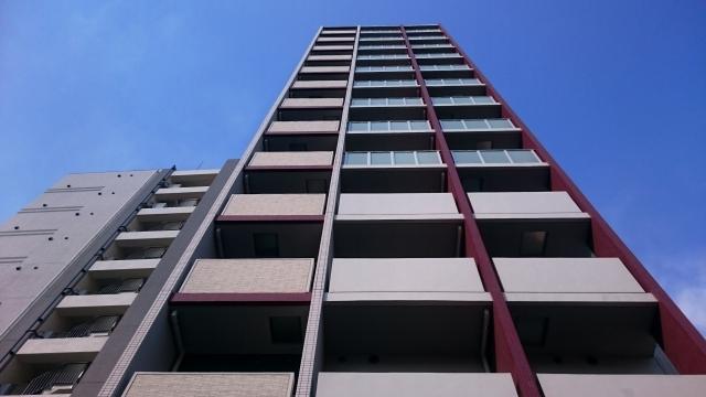 新築のタワーマンションを見上げている