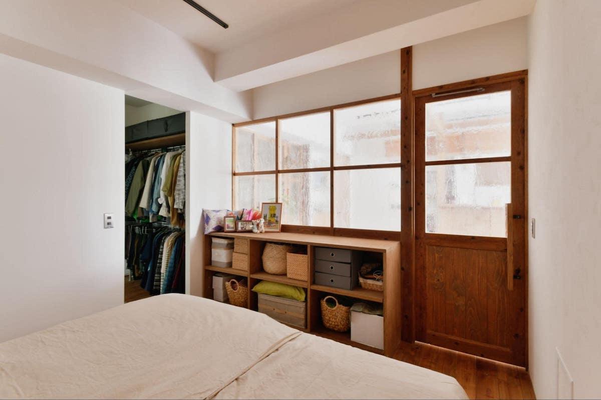 アンティークガラスの窓と珪藻土壁のある寝室
