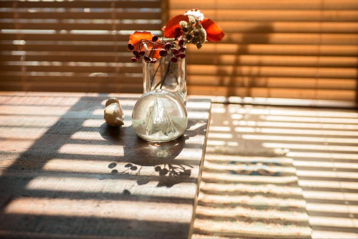 ブラインドの光とガラスの花瓶